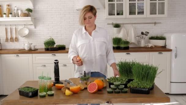 Egy fiatal nő narancslével és mikrozöldséggel készít koktélt..