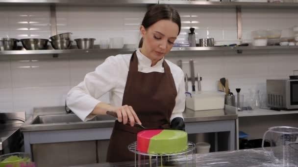 Szoros női cukrász készít egy mousse torta, szintező a tükör máz