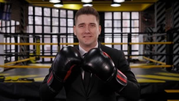 Portrait of a happy businessman in a boxing gloves in a boxing ring.