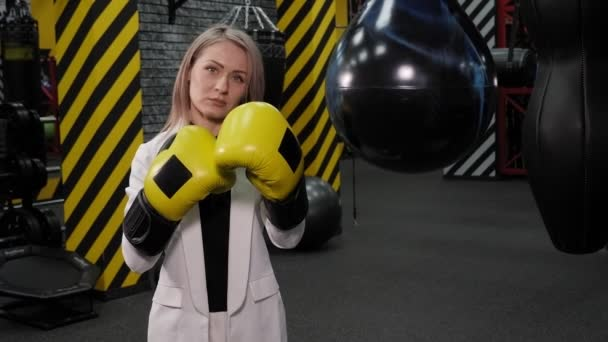 Business woman boxer in a suit and boxing gloves in the boxing ring.