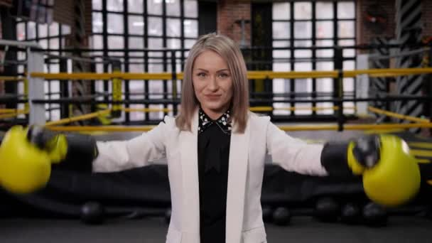 Businesswoman-boxer in a suit and boxing gloves in the boxing ring.