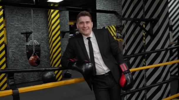 Portrait of a successful businessman in boxing gloves in the corner of the ring.