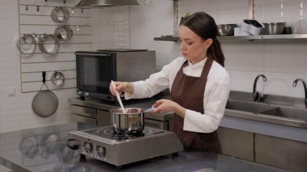 Eine Frau bereitet Pistazienmousse in einem Topf zu, rührt das Mousse mit einem Spachtel um