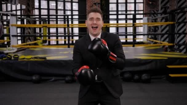 Portrait of a happy businessman in a boxing gloves in a boxing ring, he dances.