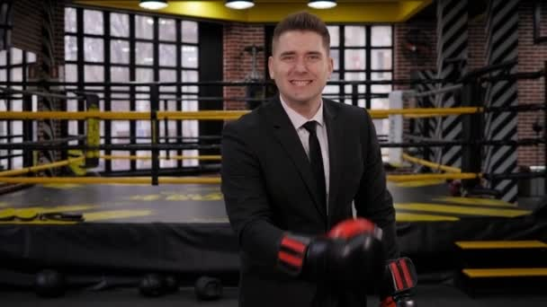 A happy successful businessman in boxing gloves raises his hands up and laughs.