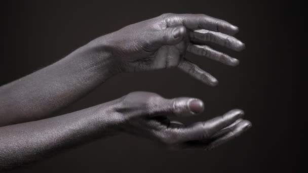 Close-up of a womans hands covered in silver paint on a black background.