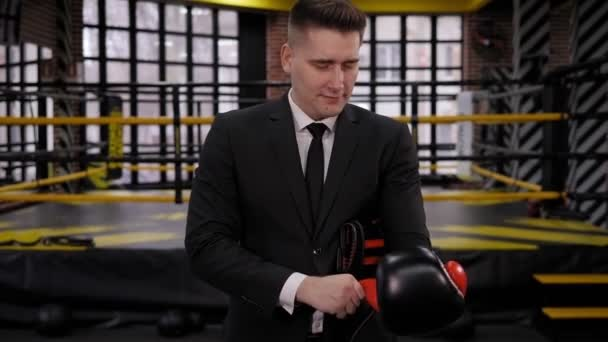 A successful businessman puts on boxing gloves while standing in a boxing ring.