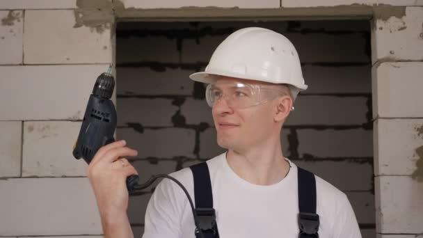 Großaufnahme eines Bauarbeiters mit hartem Hut und Schutzbrille, der einen Bohrer hält
