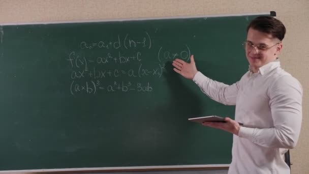 Portrait of a young student in glasses with a tablet near the blackboard.