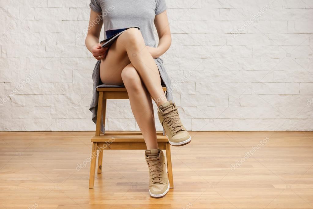 Belle gambe di una donna che legge un giornale su uno sgabello