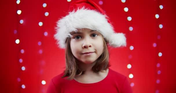 niedliches Mädchen singt ein Weihnachtslied auf rotem Hintergrund