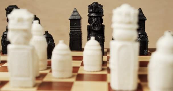 Schwarz-weiße Schachfiguren auf einem Holzschachbrett