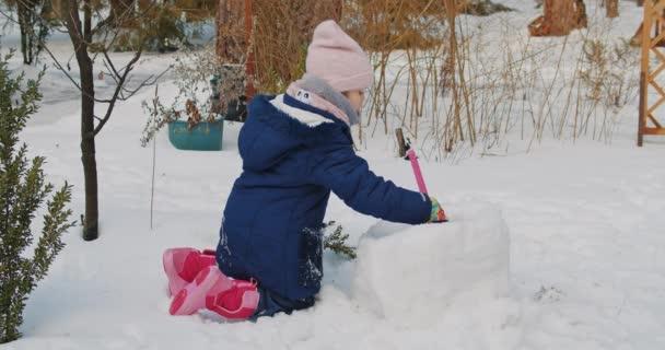 roztomilá dívka staví a hraje ve sněhu v lese