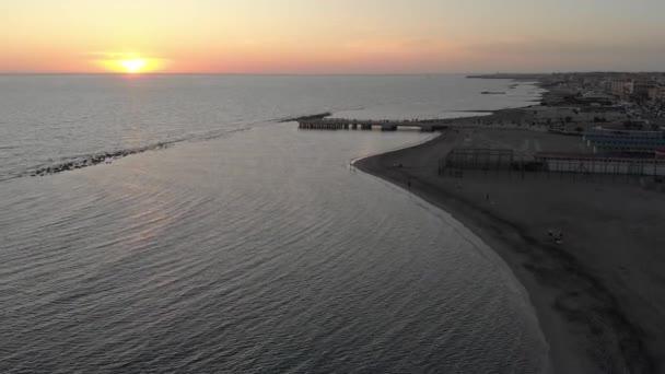 sugestivní drone pov zlatý západ slunce nad hedvábné vlnité vody moře a tmavé písečné pláže s panorama města a fantastické zlaté nebe a slunce soumrak zasáhl moře v Římě, Itálie