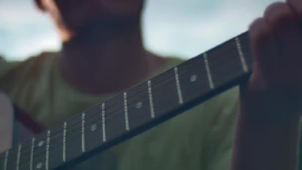 Fiatal férfi játszik akusztikus gitár