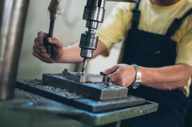 Male worker working on metalworking machine
