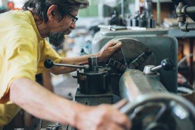 Serious man working on metalworking machine
