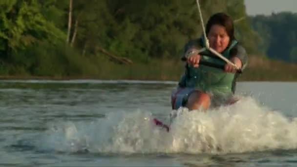 Detailní záběr záběr wakeboarder dívka dělat vlny na vlnu trik na rybniční vody