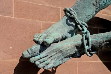 The Devils feet bound in chains (Michael and the Devil) on the wall of the new Cathedral, Coventry.