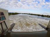 Stromschnellen unter Staudamm an der Donau. Wilde, schmutzigbraune Wassermassen unter Staudamm an der überfluteten Donau in Straubing