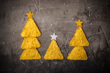 Concept of new year from mexican nachos. three Christmas trees made of chips nachos with cheese on a dark background. Copy space