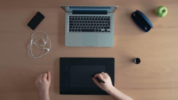 Pohled shora návrháře muž nebo illustrator používá jeho grafického tabletu a notebooku vytvoření digitálního návrhu