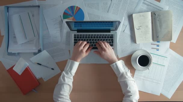 Pohled shora podnikatel pracuje v kanceláři s jeho laptop a zdůrazňuje výsečového grafu, obklopen spoustou papírování a finančních zpráv, poznámkové bloky