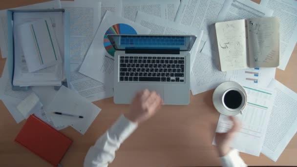 Pohled shora podnikatel pracuje v kanceláři s jeho laptop pije kávu a píše něco v poznámkovém bloku, obklopen spoustou papírování a finančních zpráv, poznámkové bloky