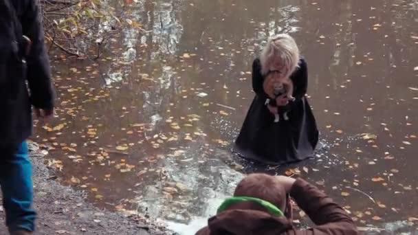 Fotografie střílet mladé ženy v charakter děsivé překližované běloška s panenkou uvnitř rybník