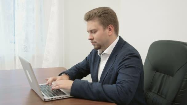 Mladý podnikatel pracuje ve své kanceláři přenosný počítač a usmívá se na kameru