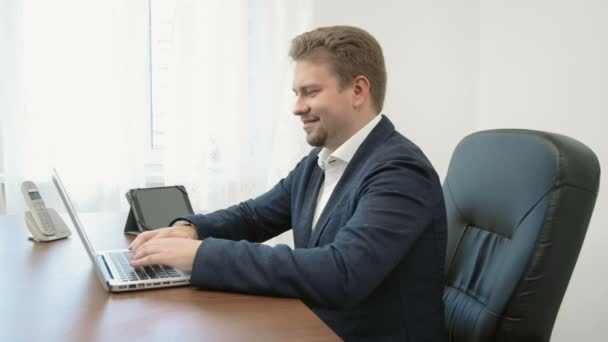 Mladý podnikatel pracuje ve své kanceláři u přenosného počítače. Usmívá se a baví, je velmi šťastný o své práci, pak turnu kamery ukazuje palec nahoru a usmívá se