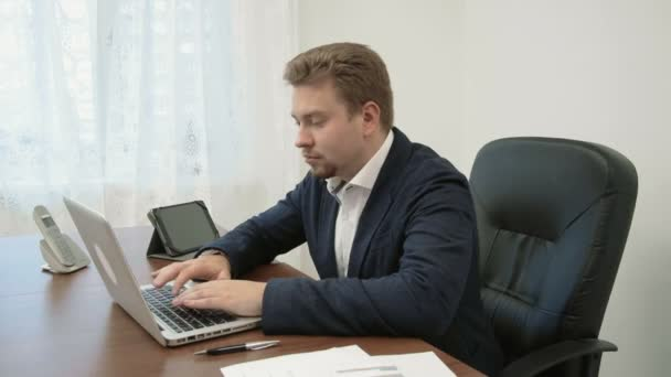 Young businessman working in his office in front of the laptop computer. He is typing and something goes wrong, he did not expect it and really suprised and sad, unhappy, depressed and unfortunate.