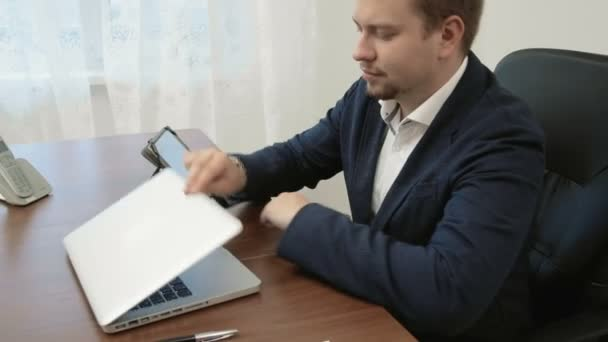 Mladý podnikatel pracuje ve své kanceláři před přenosný počítač pak bere jeho digitální dotykový tablet a začne ji používat.