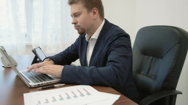 Young businessman working in his office in front of the laptop computer typing. He looks at his watch checking time, cleans up his desk and goes home because his work day is over