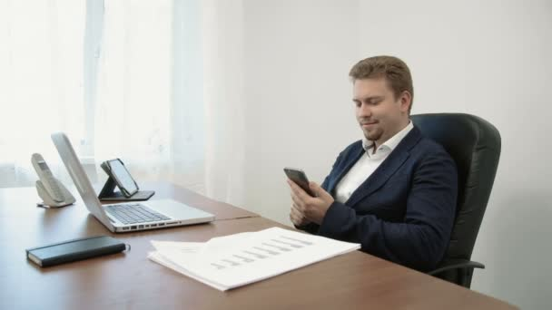 Young businessman working in his office in front of the laptop computer. He uses his smarphone touching the screen with his finger exploring business app.