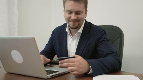 Mladý podnikatel dělá on-line nakupování ve své kanceláři a usmívá se držení platební karty a zadáním jeho čísla na webu
