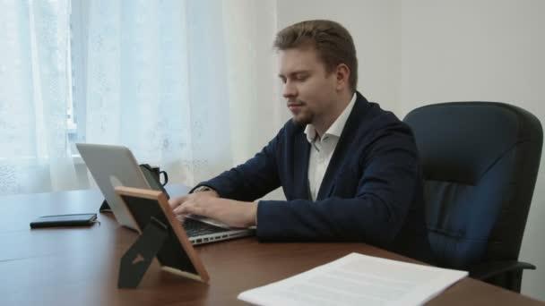 Mladý podnikatel pracuje ve své kanceláři u přenosného počítače. Pak se dívá na obraz jeho rodina bere ji, úsměvy a pokračuje v práci