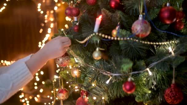 Közelkép a gyerek kezét díszítő karácsonyfa golyókat a háttérben fényes ünnepi fények. karácsonyfát díszítő gyerekek.