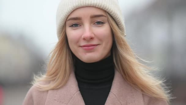 Close-up portrait of a young girl in a coat and hat stands on a city street. Enjoying fresh cold air on nature with smile