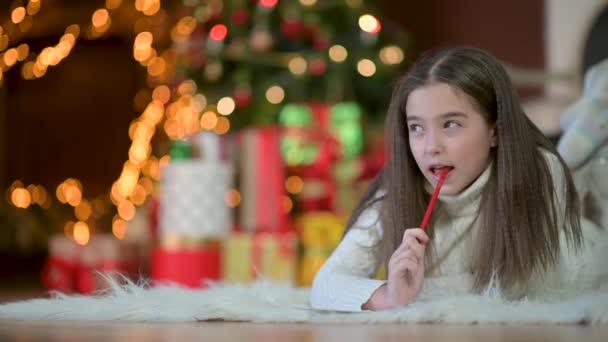 Na podlaze leží portrét roztomilé holčičky a na pozadí slavnostního vánočního stromku píše dopis pro Santa Clause. koncepce svátků a oslav