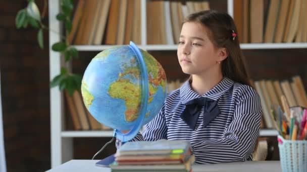Hallgató gyermek Földgömböt tanul a könyvtárban. Iskoláskorú gyermek