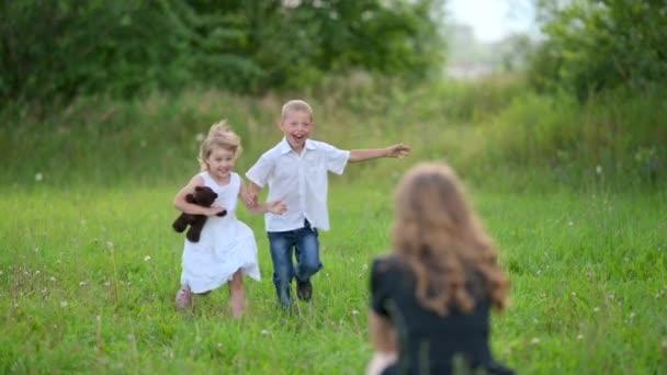 Šťastné děti radostně vběhnou do mámina objetí. Mladá máma objímá milované děti v letním parku. Zpomal. Šťastný rodinný koncept.