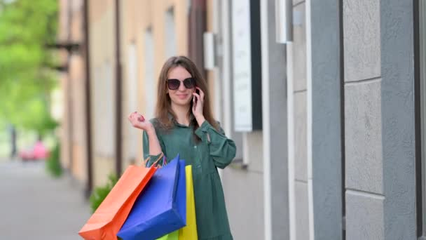 Glückliches Mädchen in einem Kleid mit Sonnenbrille und Einkaufstüten auf einer Straße in der Stadt. Junge Frau, die auf der Straße steht und ihr Handy benutzt. Stadtentwicklungskonzept