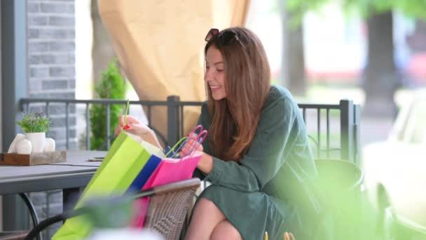 Glückliches Mädchen in einem Kleid mit Einkaufstüten in einem Straßencafé. Die junge Frau sitzt an einem Tisch und schaut lächelnd einkaufen. Stadtentwicklungskonzept
