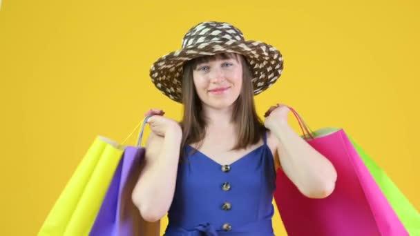 Egy kalapos fiatal lány portréja. Csomagokat tart a kezében vásárlásokkal. Nő bevásárló táskák stúdió sárga háttér. Az emberek életmódjának fogalma