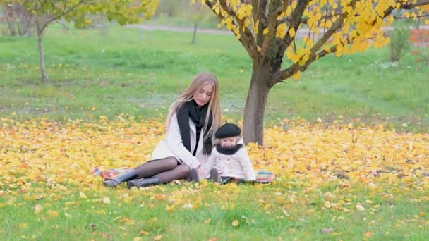 Portrait of happy mom playing with cute little daughter in autumn park. Happy family in park. Motherhood childhood concept