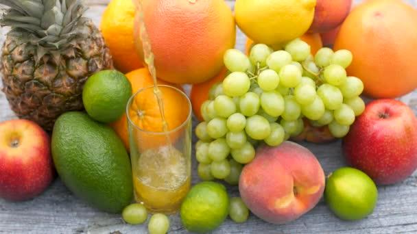 Friss gyümölcslevet öntenek egy pohárba egy fából készült asztalra a kertben, sok különböző gyümölcs körül. Egészséges étel koncepció. Gyümölcskeverék.
