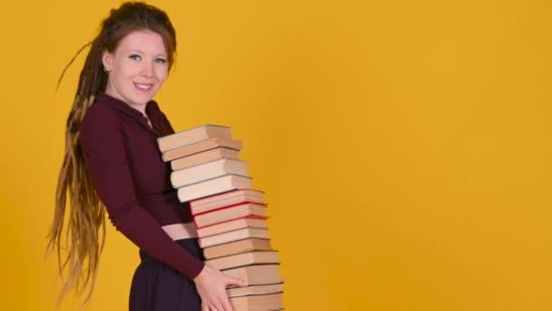 Dospívající dívka drží mnoho knih v jeho rukou izolovaných na žlutém pozadí studia.