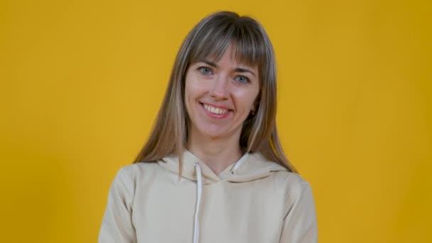 Portrét šťastné dívky usmívající se izolované na žlutém pozadí studia. Šťastná žena se dívá do kamery. Pozitivní emoce lidí.