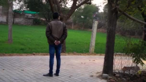 Indický mladý člen rodiny stojí na ulici a těší DJ hudby na příležitostném festivalu.